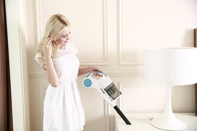 a woman using a cordless vacuum cleaner